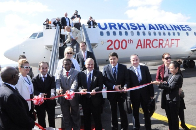 The Ministry of Transport Permanent Secretary John Mngodo (fourth left) cuts a ribbon to launch the Turish Airlines Instabul-Kilimanjaro route at Kilimanjaro International Airport yesterday. Third left is the Turkish Airlines President and CEO Dr.Temel Kotl. Photo by Staff photographer.